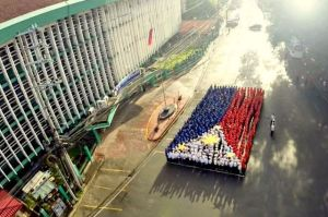 Employees of the Bureau of Immigration form the flag of the Philippines during the agency's anniversary in 2014. BI/Released, file